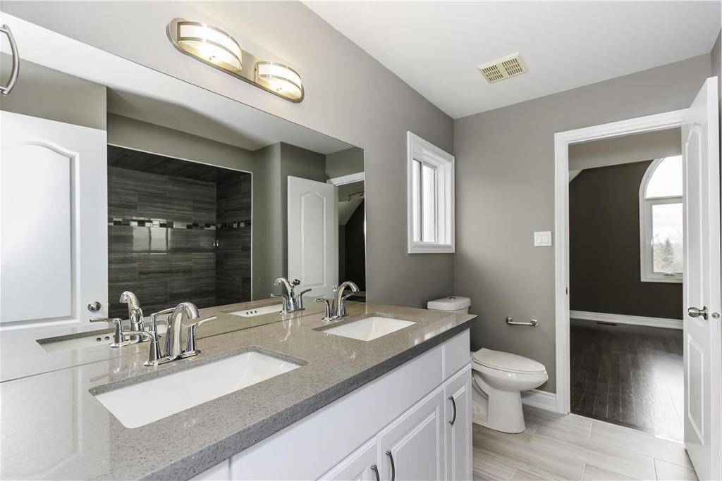 Un bagno con il grande vano doccia (che si vede nello specchio) ricavato dallo spostamento di un tramezzo